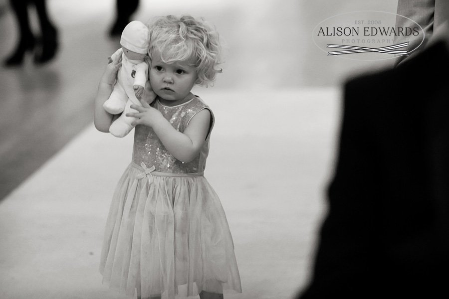 little girl holding teddy during wedding ceremony