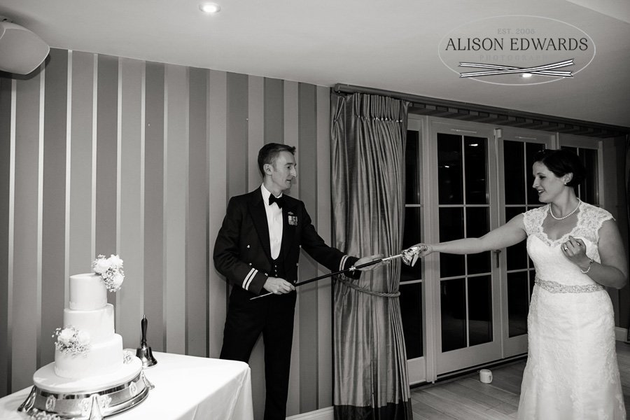 bride and groom cutting cake with military sword