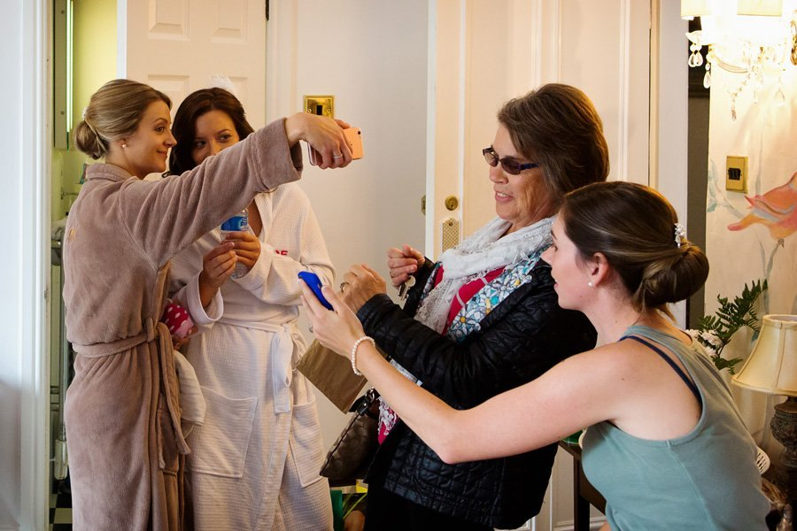 bridesmaids and family taking selfies while bride gets ready