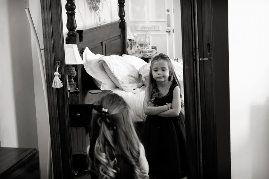 flower girl looking in mirror at her bridesmaid dress