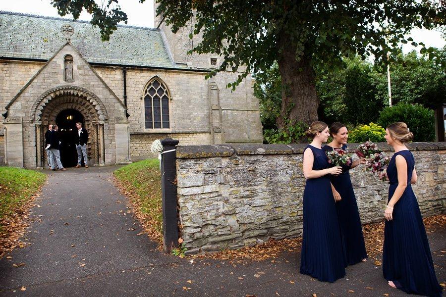 bridesmaids and groomsmen waiting at church for bride