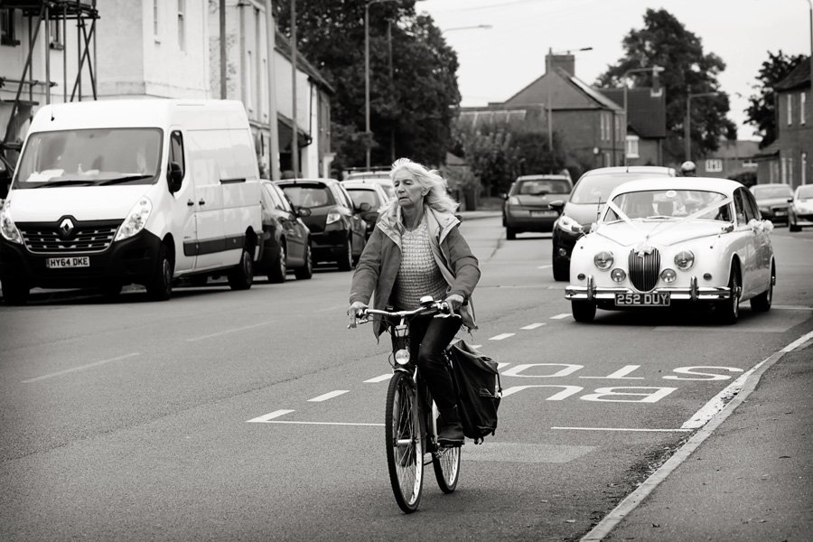 woman cycling in front of bride's wedding car arriving at church