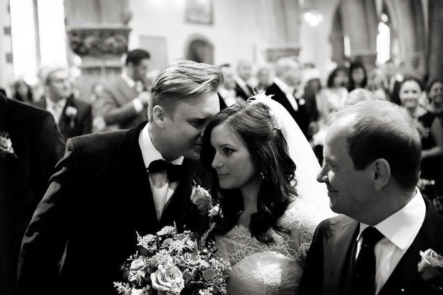 groom kissing bride in church