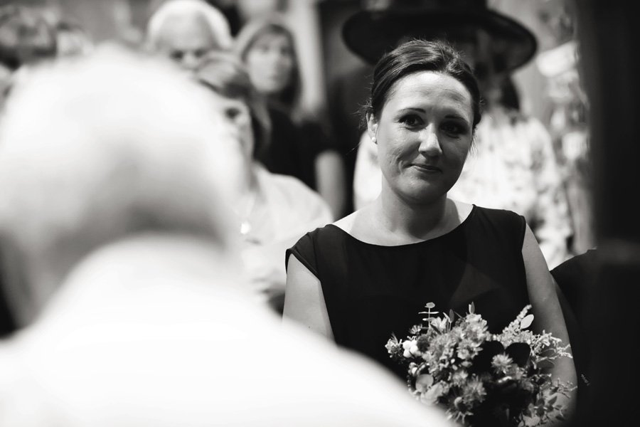 bridesmaid looking at bride and groom in church