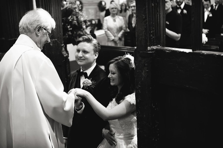 bride and groom being blessed by vicar