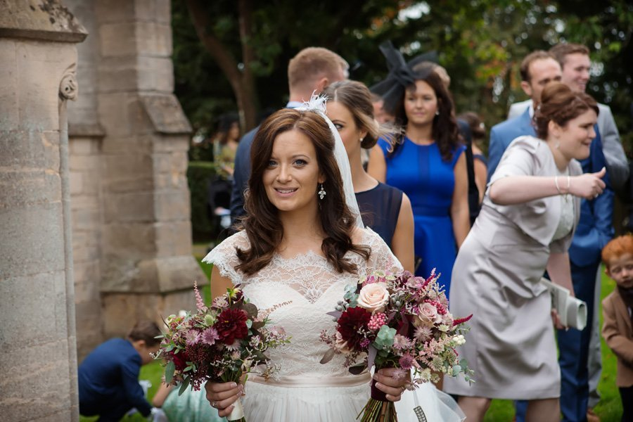 bride coming out of church with guests