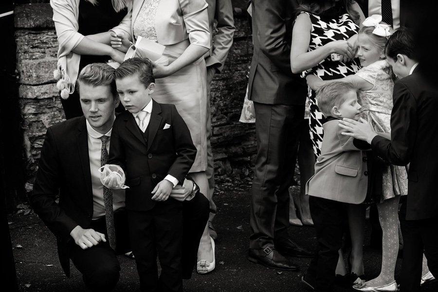guests watching bride and groom in wedding car