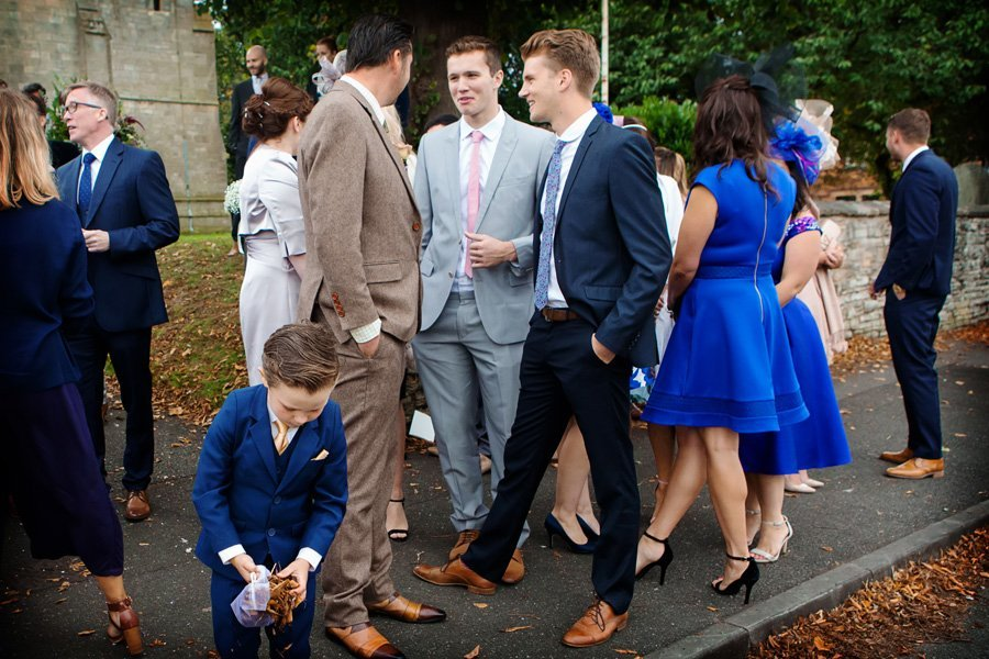 boy collecting leaves outside of church after wedding