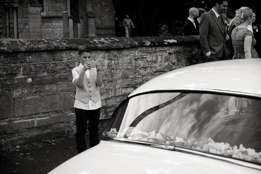 boy talking photo of bride and groom in wedding car