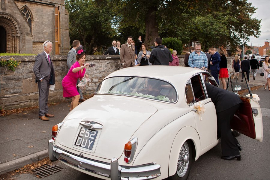 guests taking photo of bride and groom in wedding car