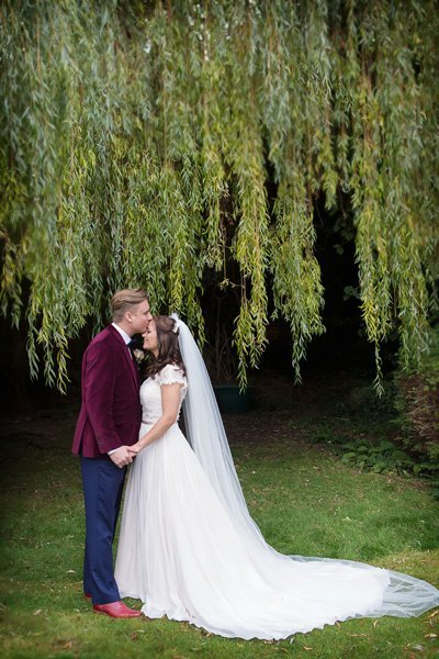 groom kissing bride's forehead in gardens Newark