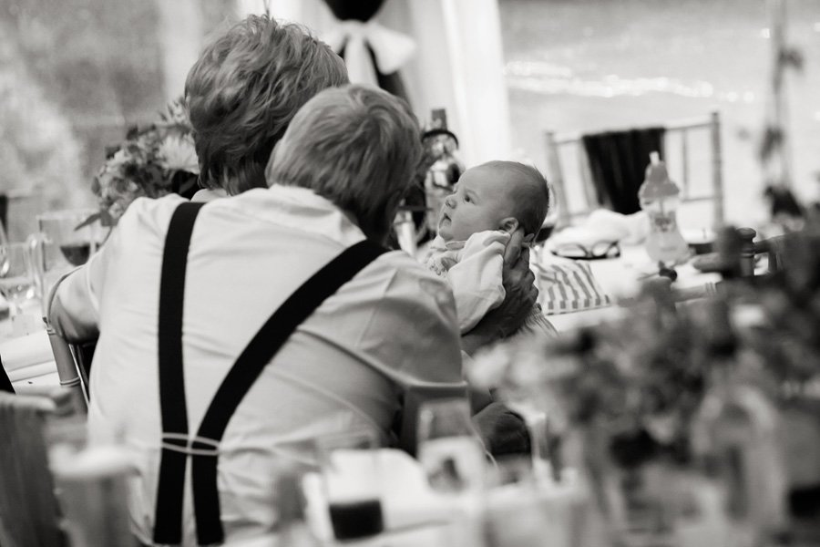 grandparents holding baby at wedding