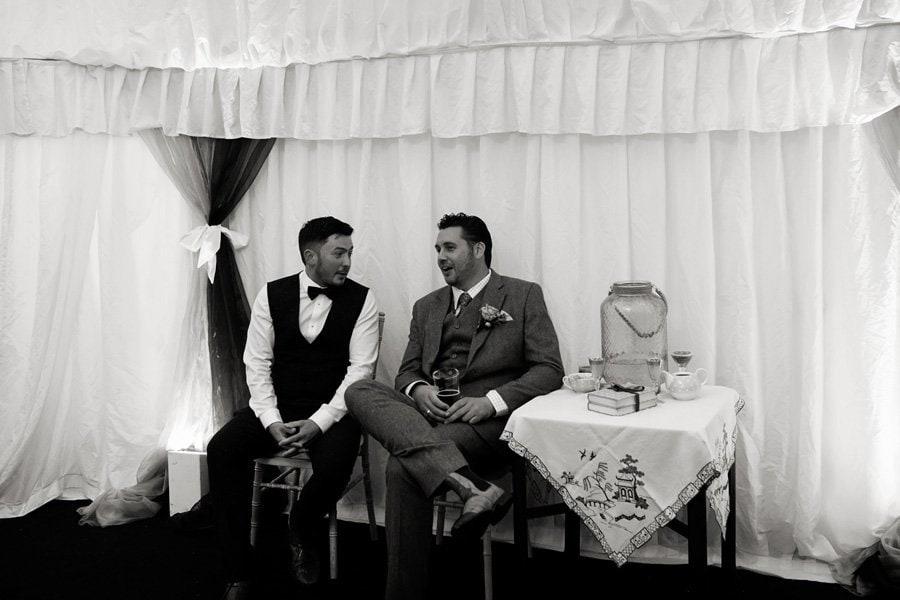 two men sitting talking at wedding