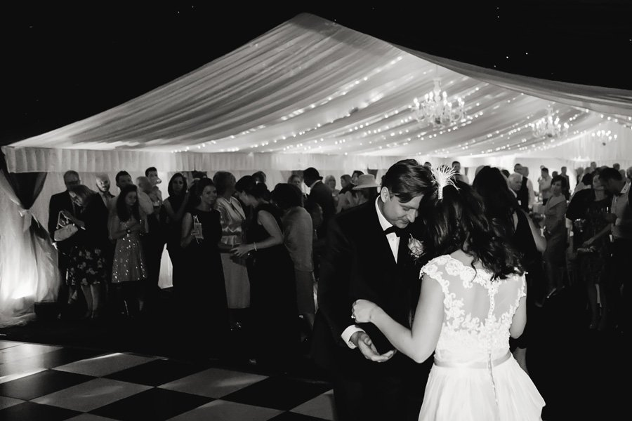 bride and groom's first dance with guests watching in marquee
