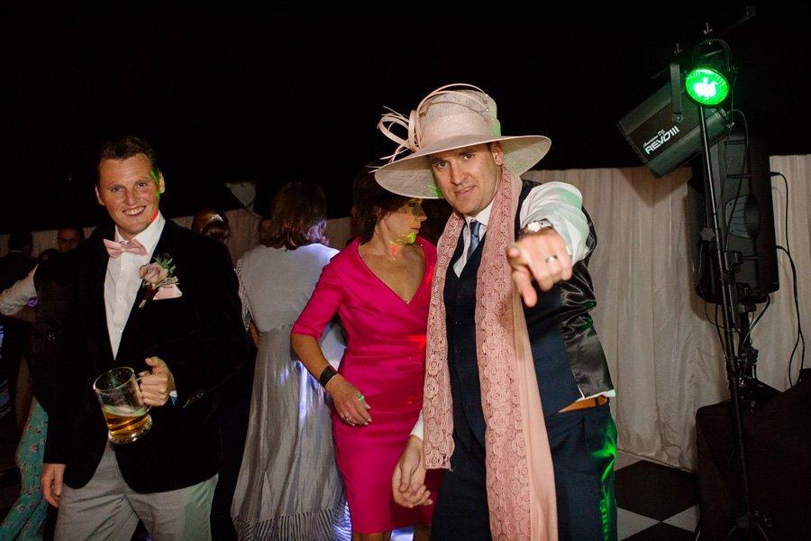 Man wearing women's hat at wedding