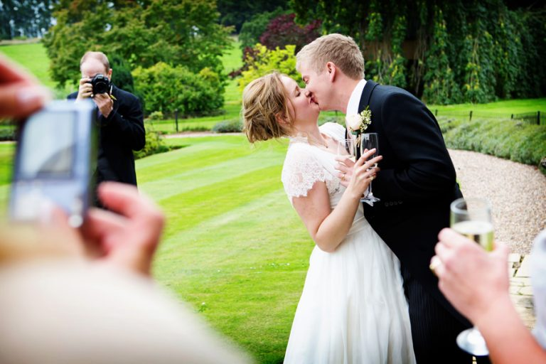 bride and groom kissing with people taking photo