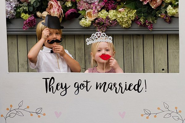 two children in polaroid style photo as bride and groom