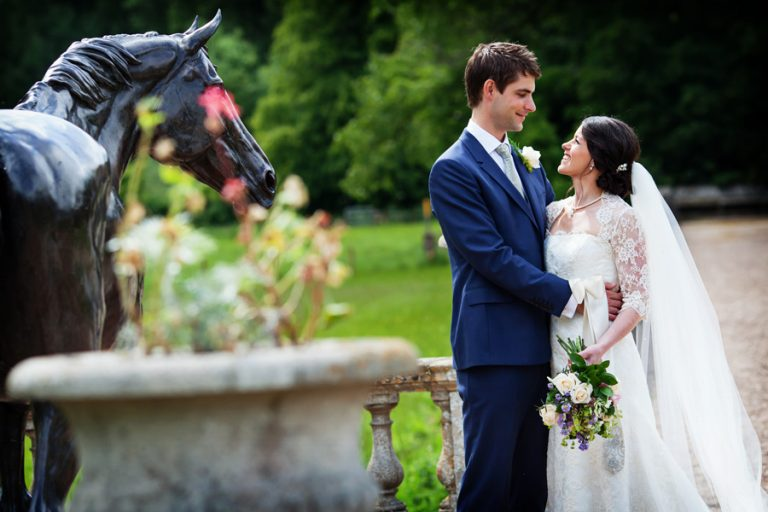 bride and groom near horse statue at Prestwold Hall