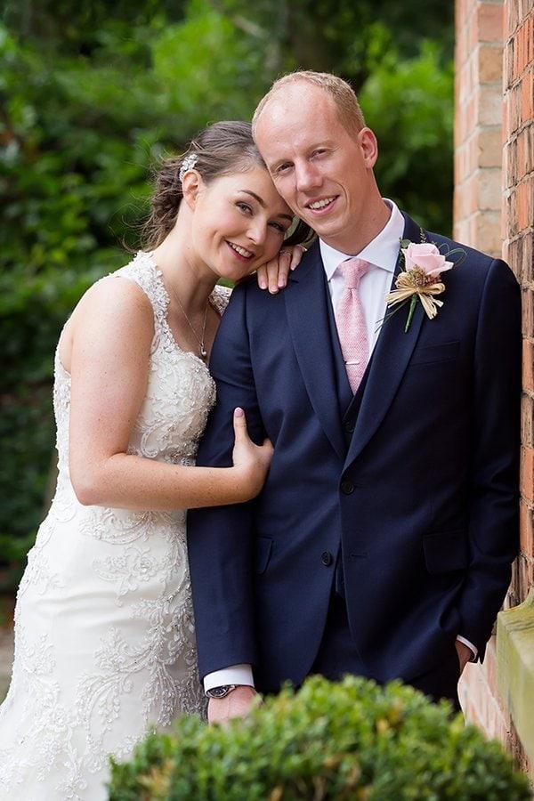 bride leaning on groom's shoulder at Norwood Park smiling