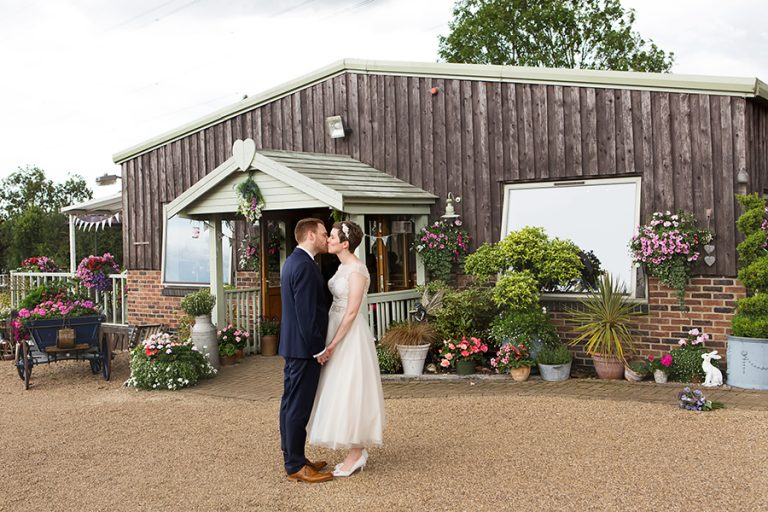 bride and groom kissing in front of barn at Floral Media