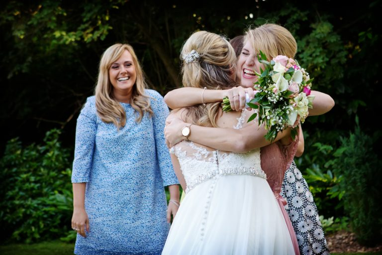 bridesmaid hugging bride after catching bouquet