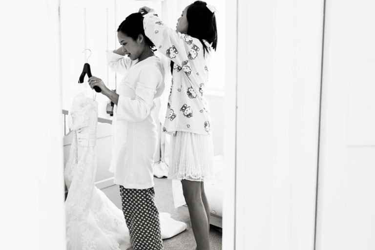 bride being helped with hair piece before wedding