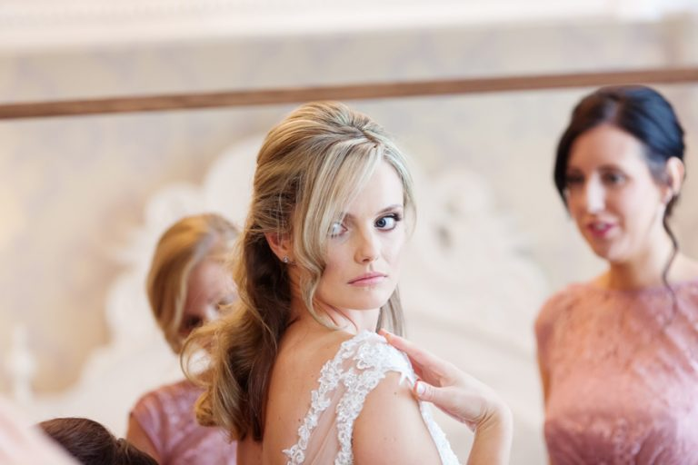 bride looking in mirror checking back of wedding dress