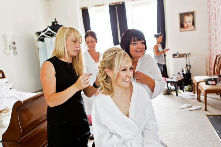 bride and bride's mum laughing in bedroom having hair done
