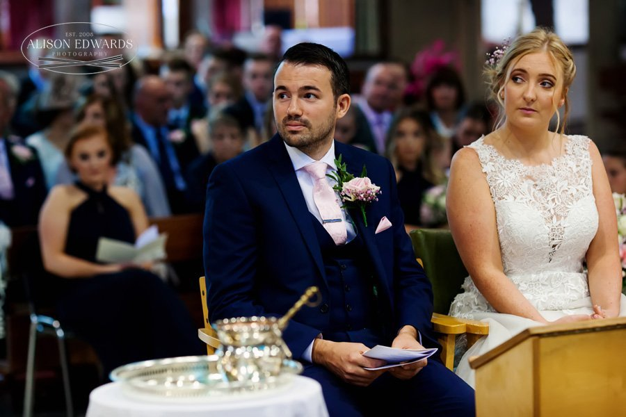 bride and groom sitting in church listing to reading