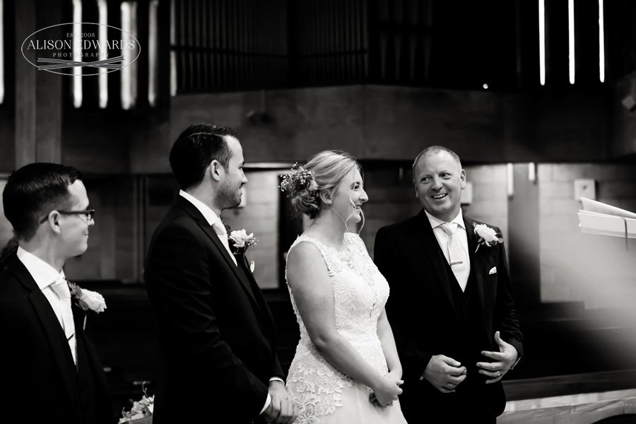 bride's dad smiling at bride and groom in church
