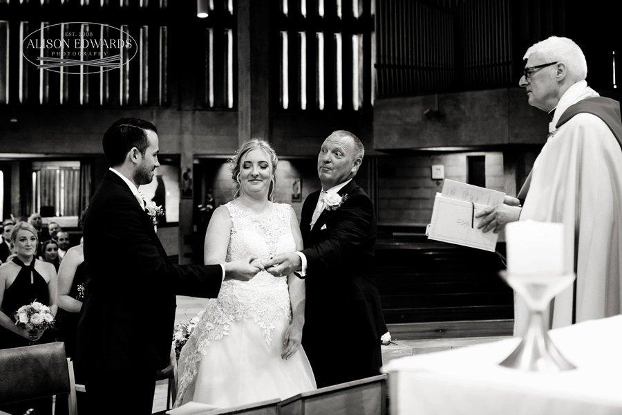 bride's dad handing over daughter's hand to groom in church