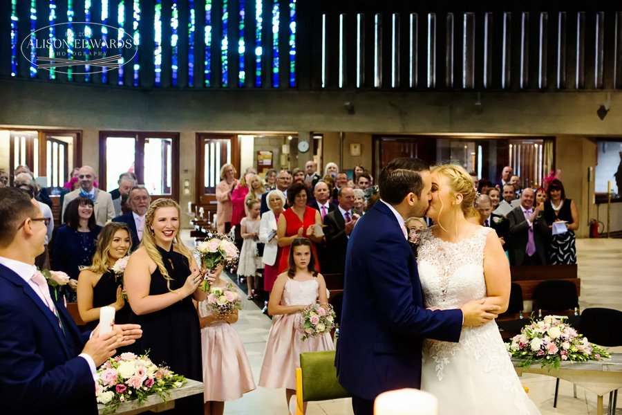 bride and groom kissing in front of congregation