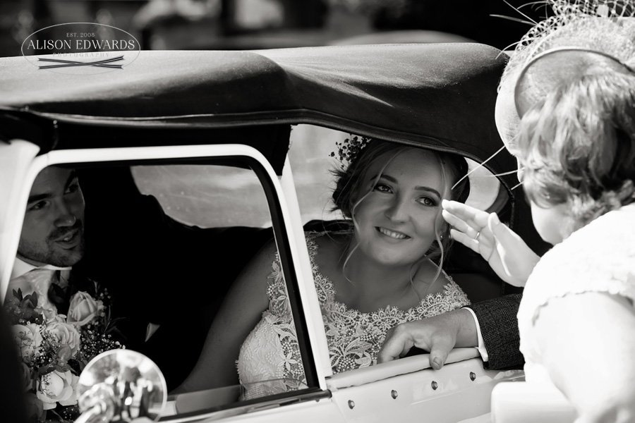 bride talking to wedding guest in wedding car