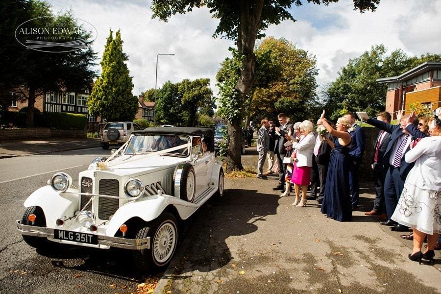 bride and groom leaving church in wedding car guests waving