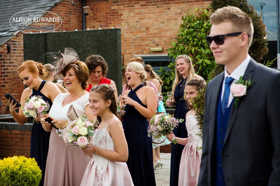 wedding guests laughing with bride and groom arriving at Goosedale