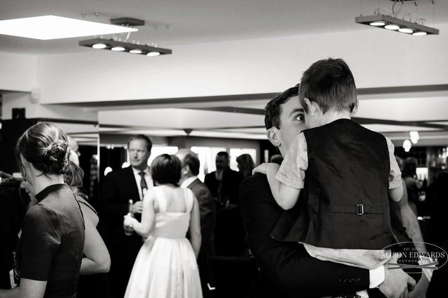 wedding guest picking boy up in drinks reception