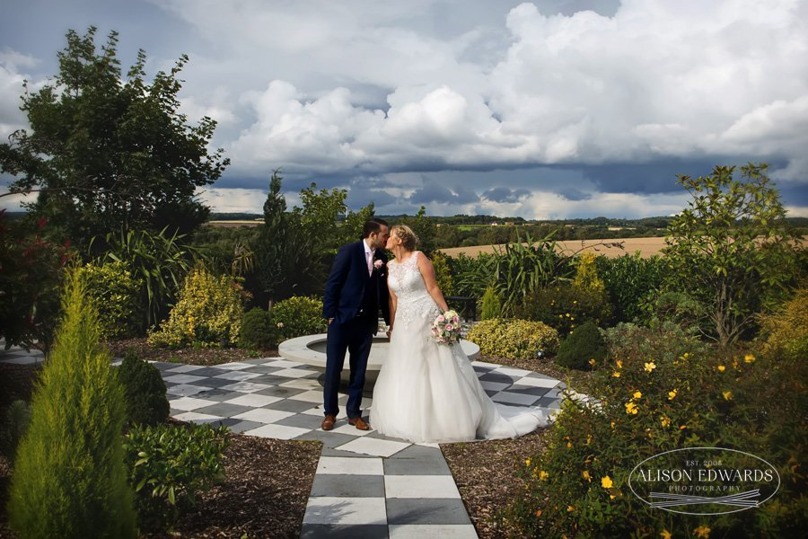 bride and groom kissing in gardens at Goosedale