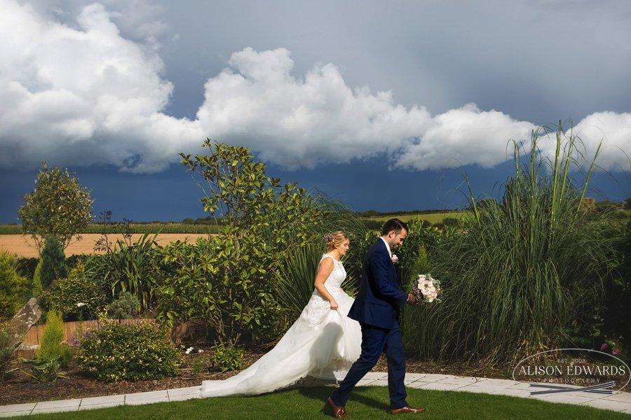bride and groom walking across Goosedale gardens