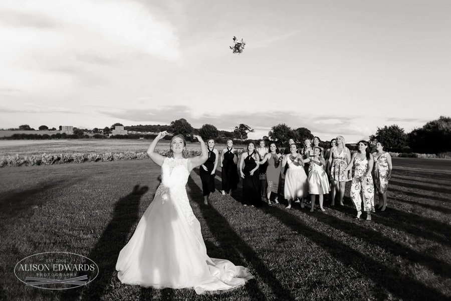 bride throwing bouquet in field at Goosedale