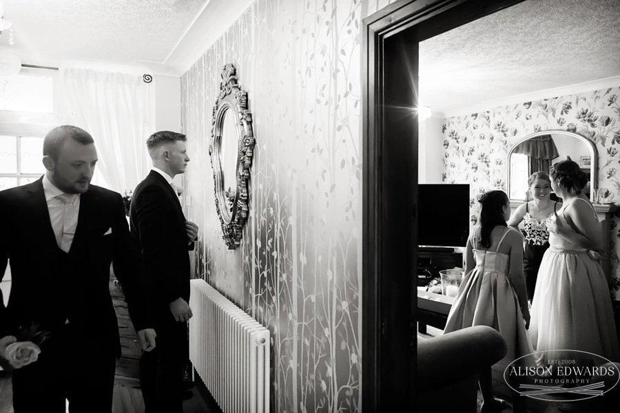 ushers looking through mirror in hallway bridesmaids talking in living room