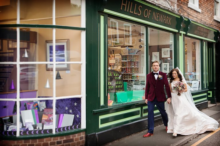 nottingha wedding portrait of bride and groom walking past bookshop in newark