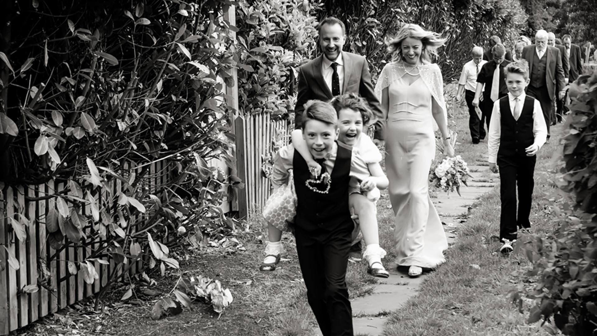 wedding guests walking from church children giving piggy back in front of bride and groom