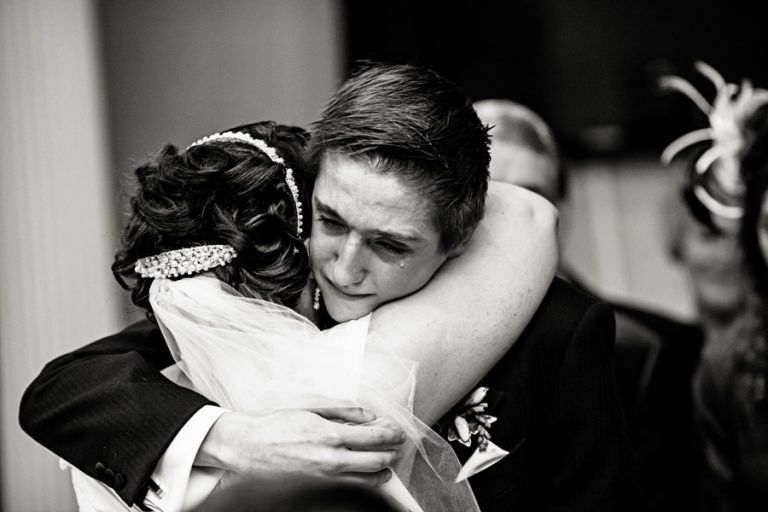 bride hugging her son who had tear running down his face