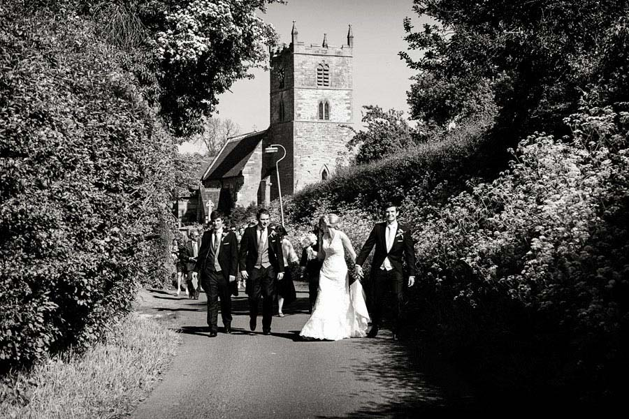 bride and groom walking up lane from church with wedding guests