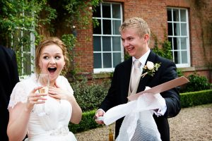 bride with surprised face as groom opens champagne sword gift