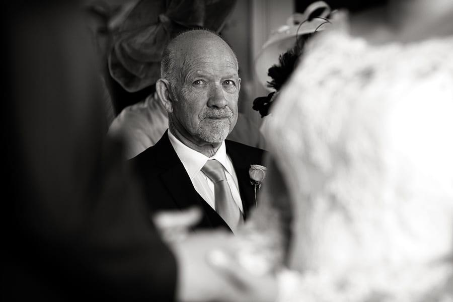 bride's dad looking at bride and groom during wedding vows