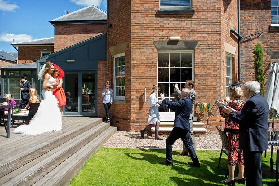 guests taking photos of bride
