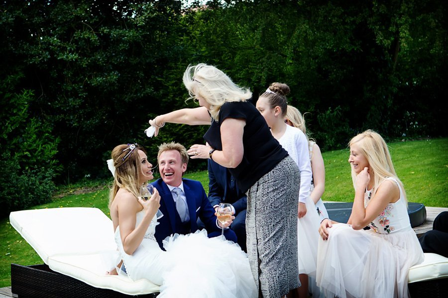 guest pouring confetti over bride and groom