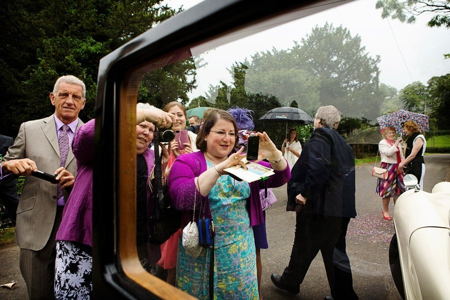 Stoke Rochford Hall Wedding Photographer captures guests taking photos of bride and groom in car a