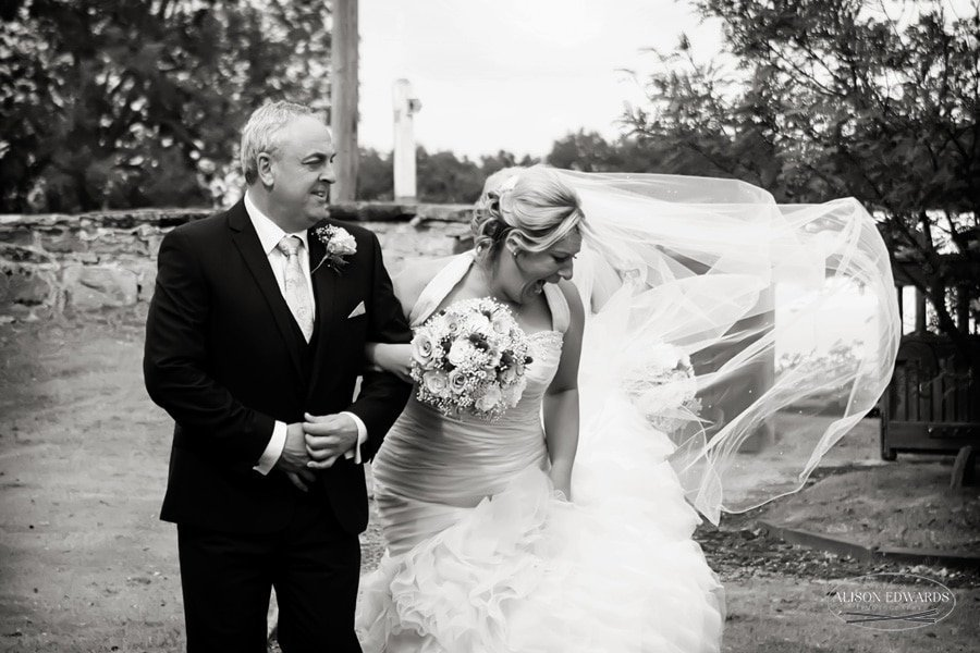 bride and father at church veil blowing in wind